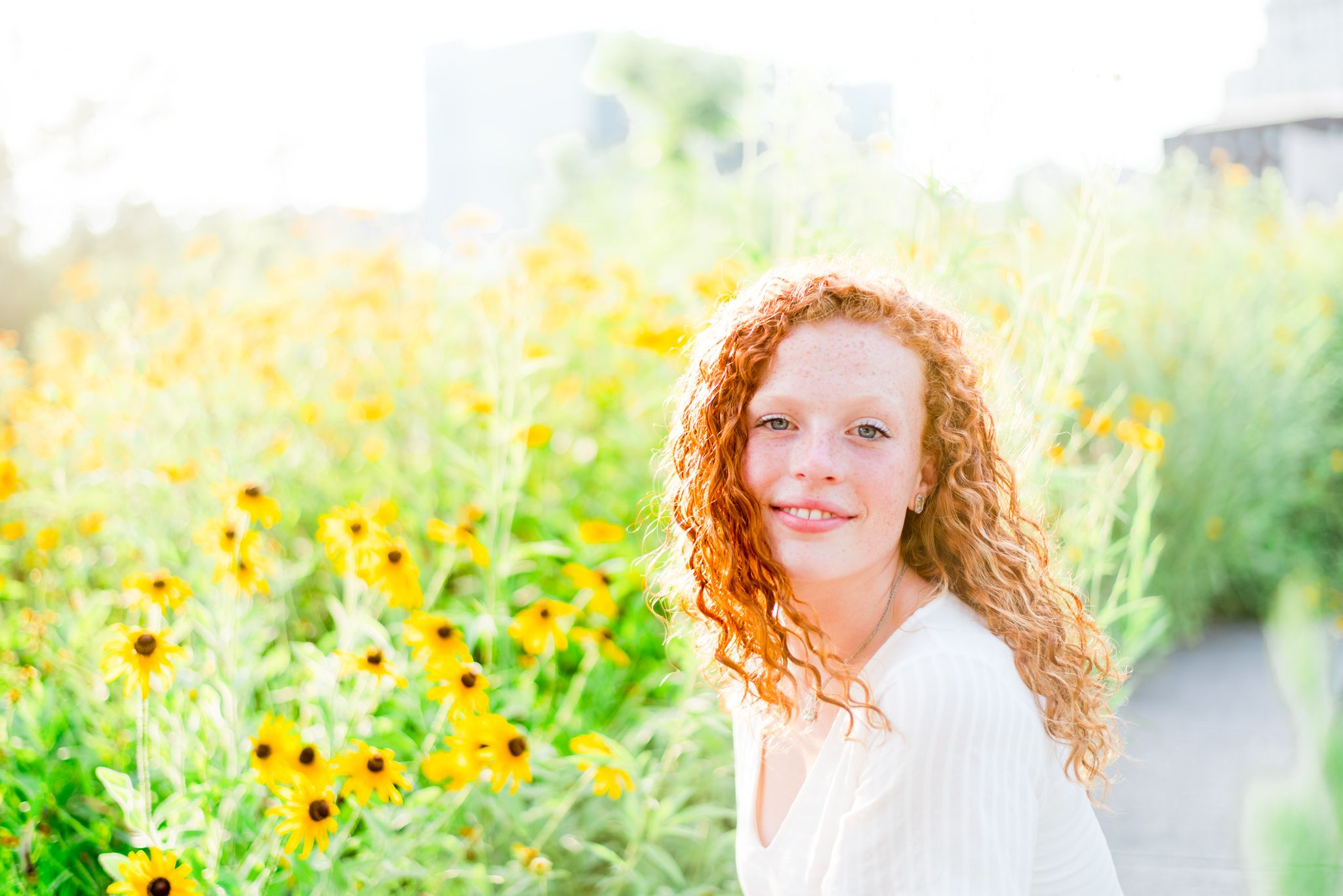young woman with red curly hair softly smiles in front of black eyes susan flowers in Smale Park