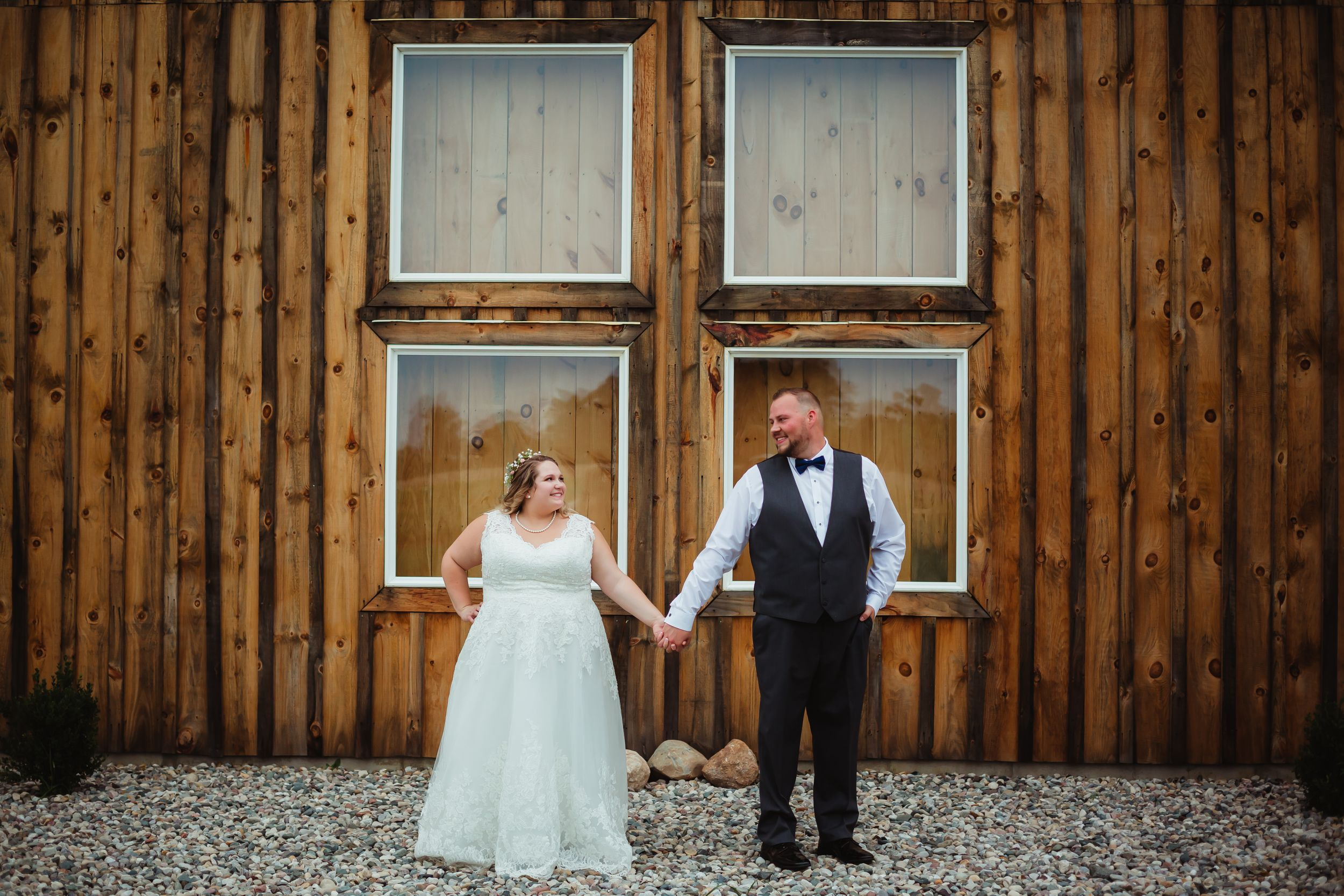 Bride and groom holding hands smiling at each other standing in front of four windows on a barn.