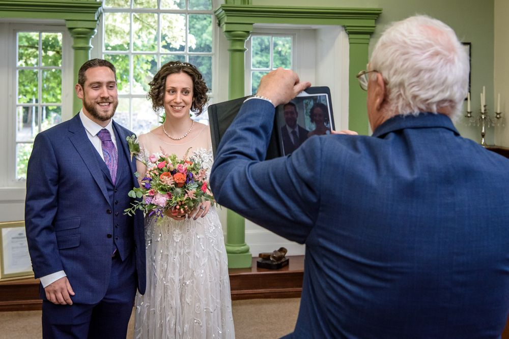 Bride's father taking picture of just married couple