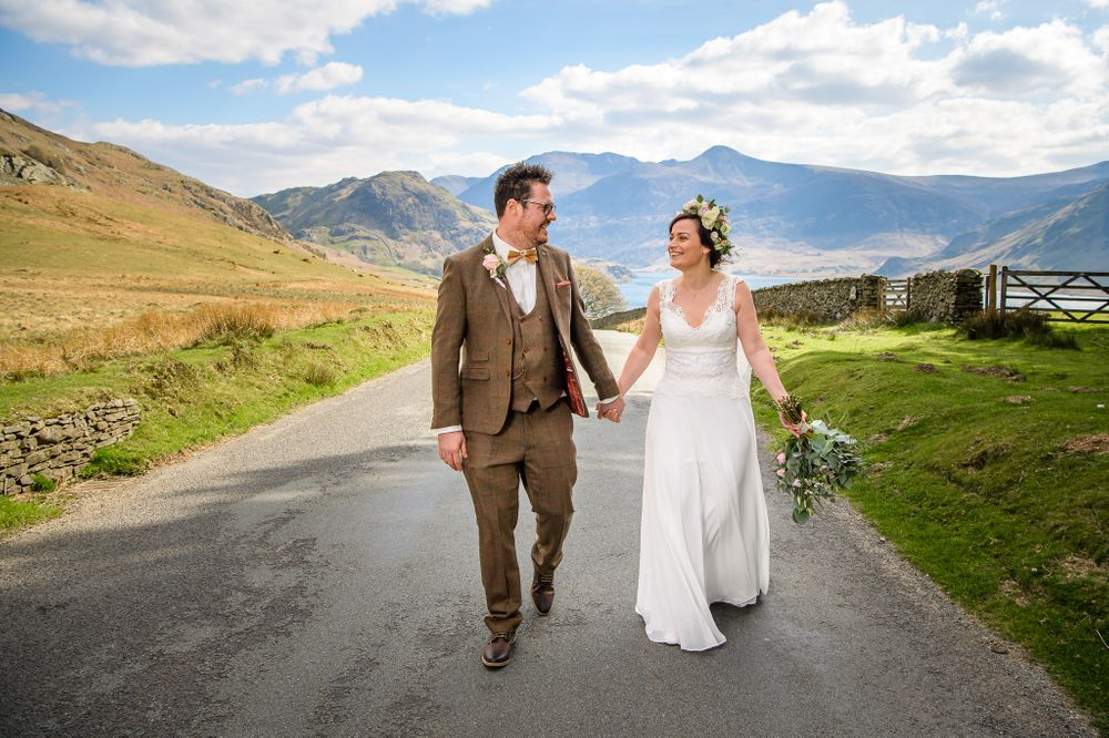 Bride and groom walk along road near Crummock Water in Lake District
