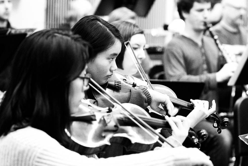 Young musicians of the Seattle Collaborative Orchestra focus intently during rehearsal.