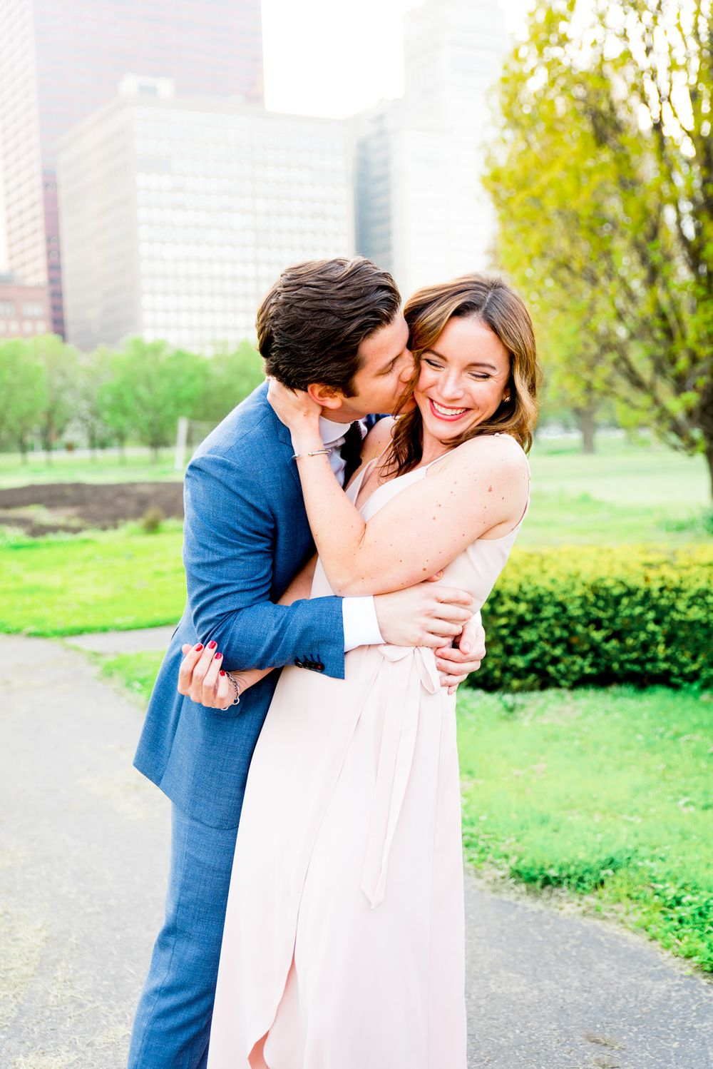 man in navy suit hugs and kisses fiancee in pink dress who is smiling in Millennium Park Chicago engagement