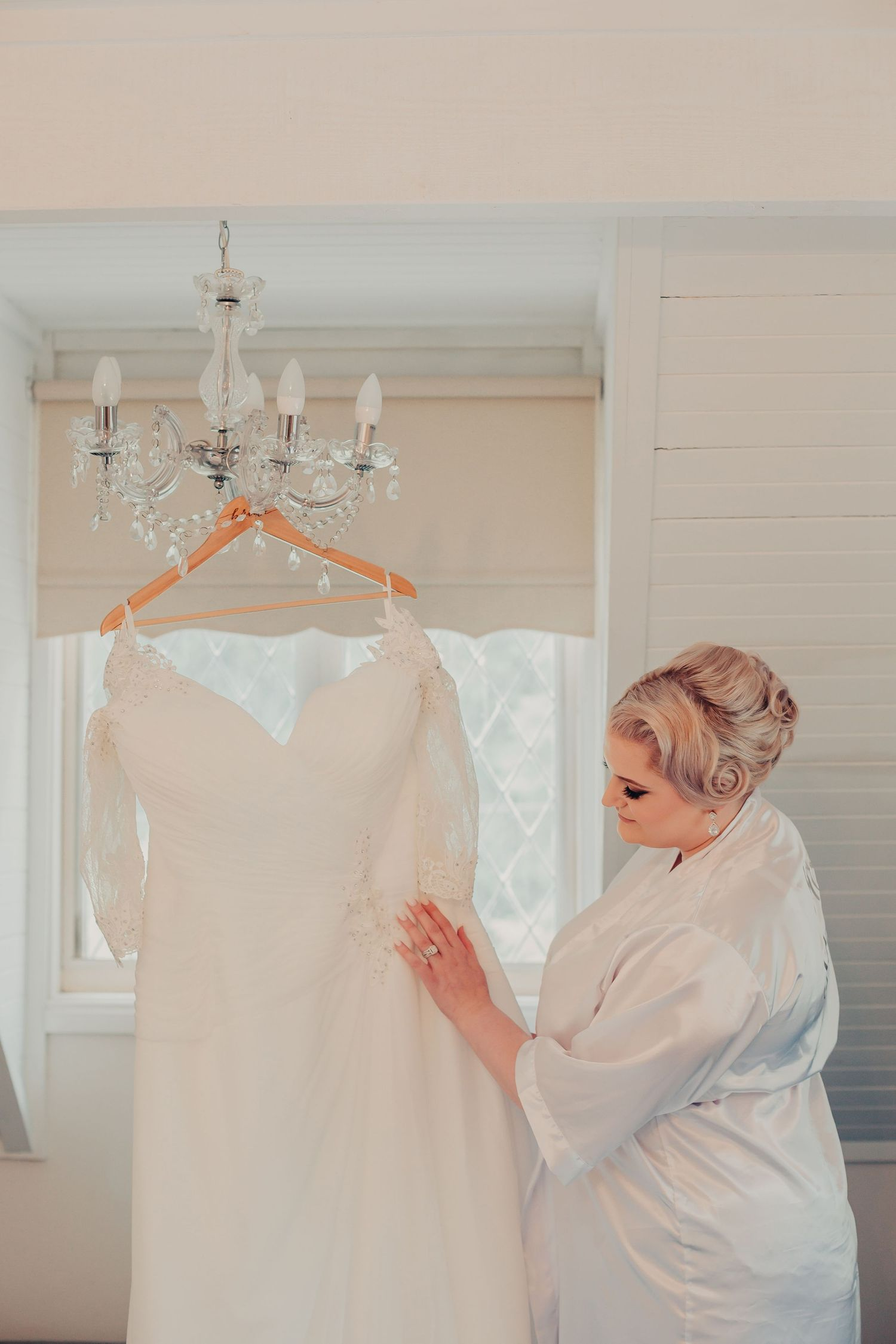 Bride in robe looking at wedding gown vintage style elopement meloburne wedding photography