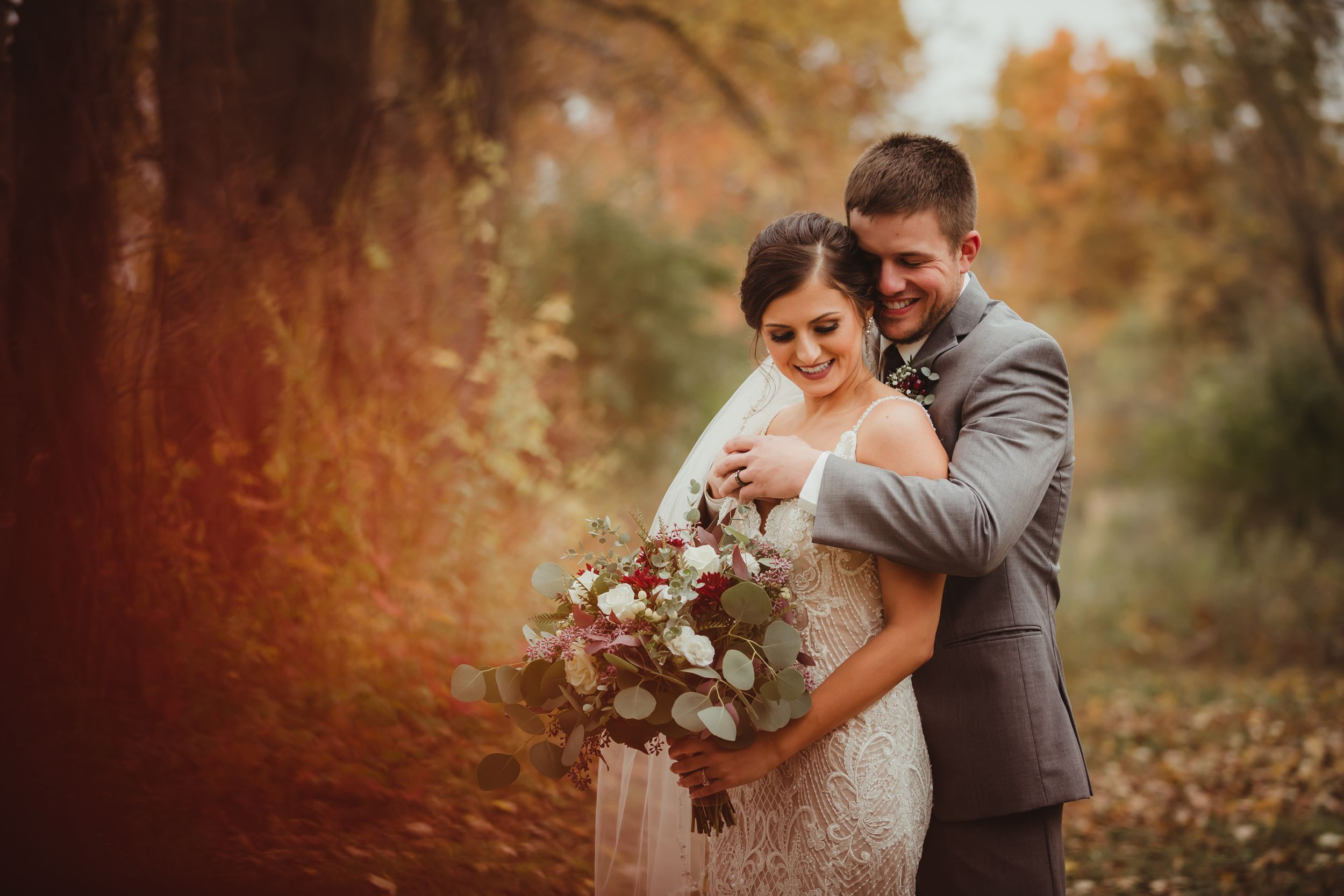Groom standing behind bride hugging around her shoulders and chest while they smile. There is bright fall foliage.