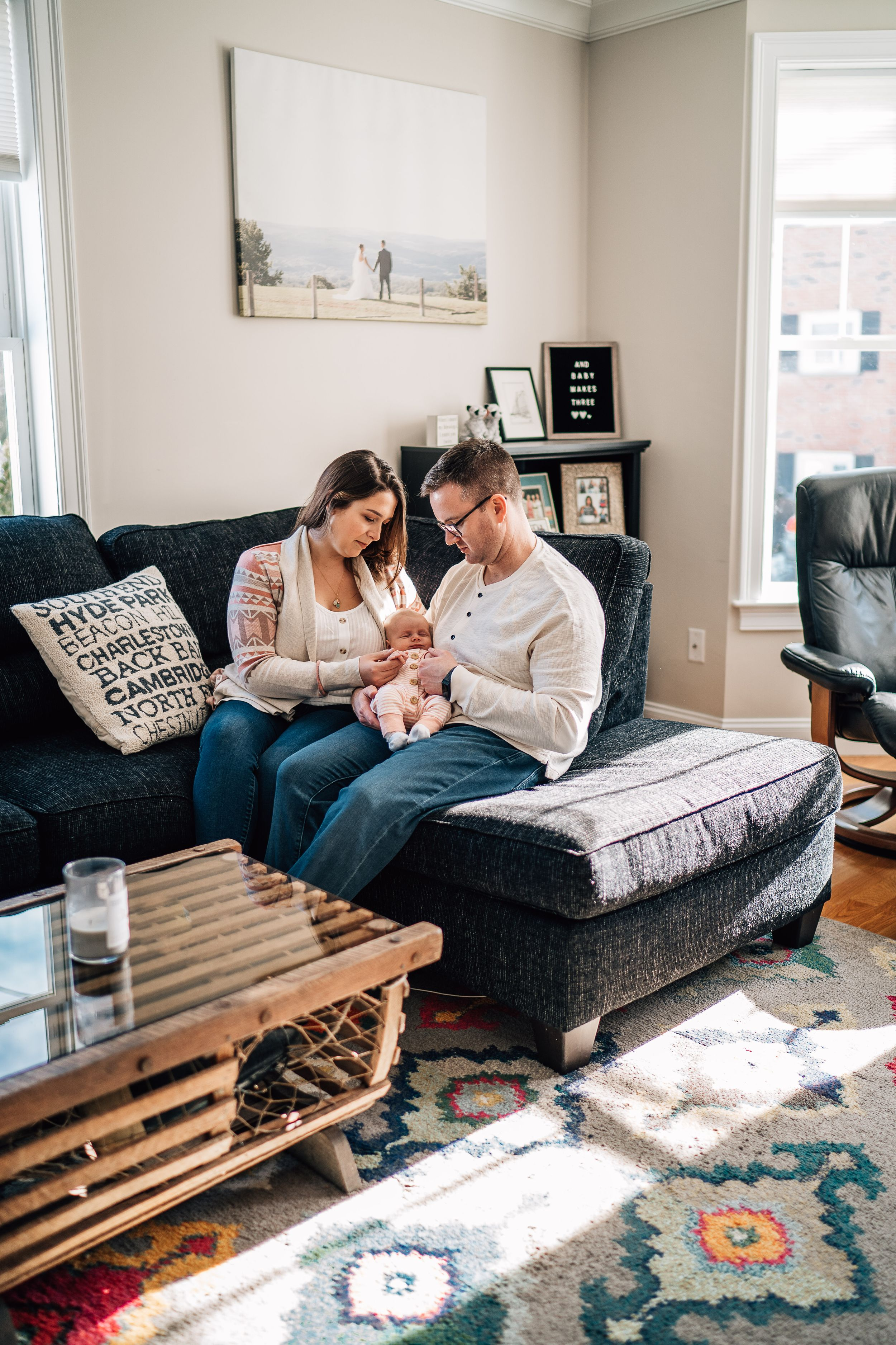 parents holding their baby in their boston living room