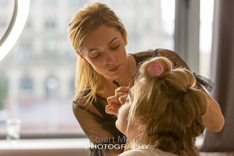 one of the bridesmaids having her hair done by the makeup artist