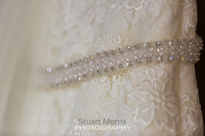 detail shot of the brides dress and belt hinging up from the wardrobe