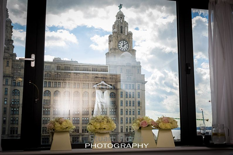 reflection of the brides dress in the hotel window the liver building outside the hotel bouquets on the window sill