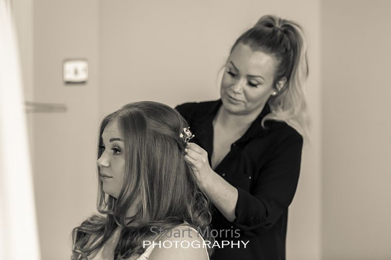 bridesmaid sitting down as the hairdresser does her thing