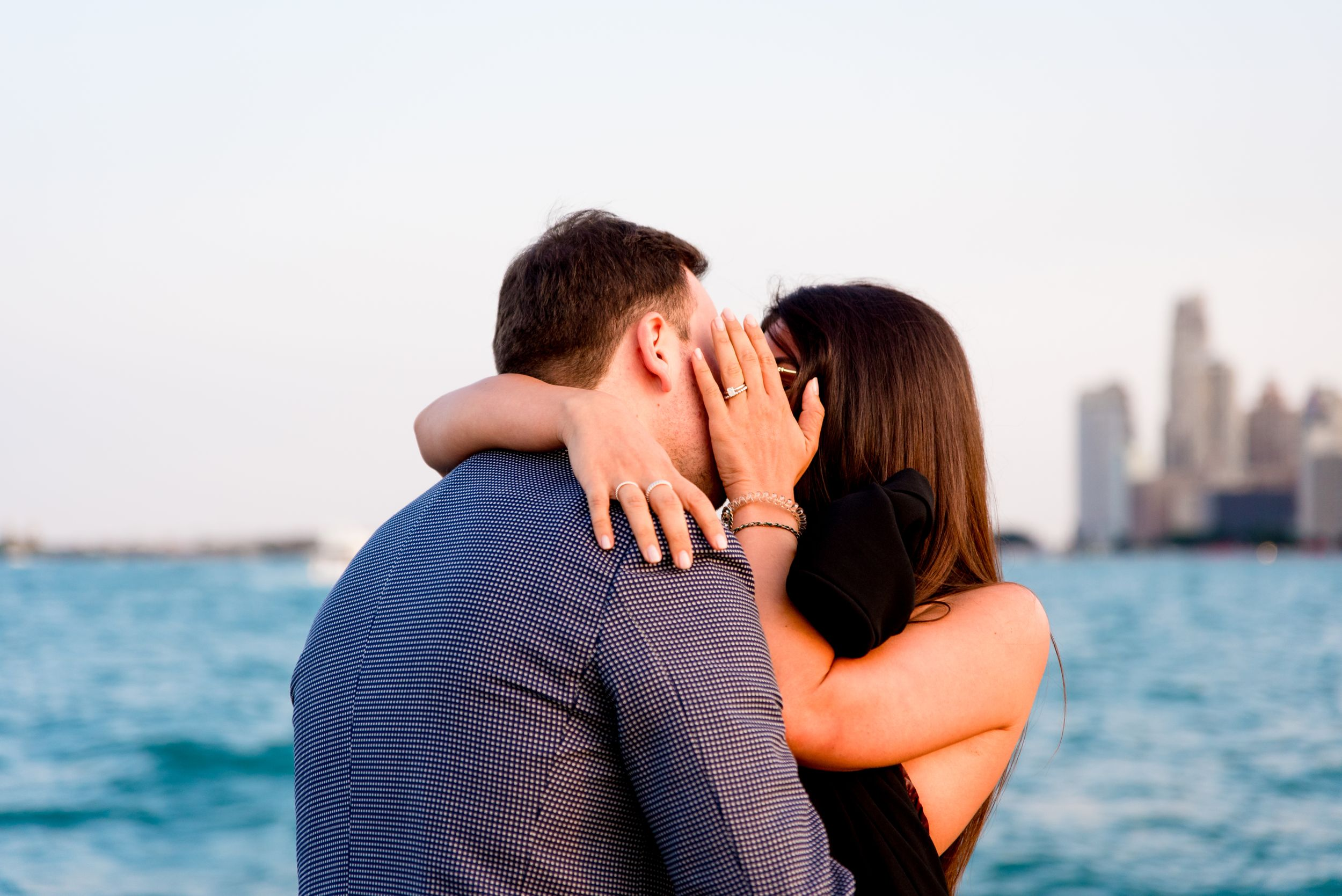 man and woman kissing after Chicago proposal at North Avenue Beach pier