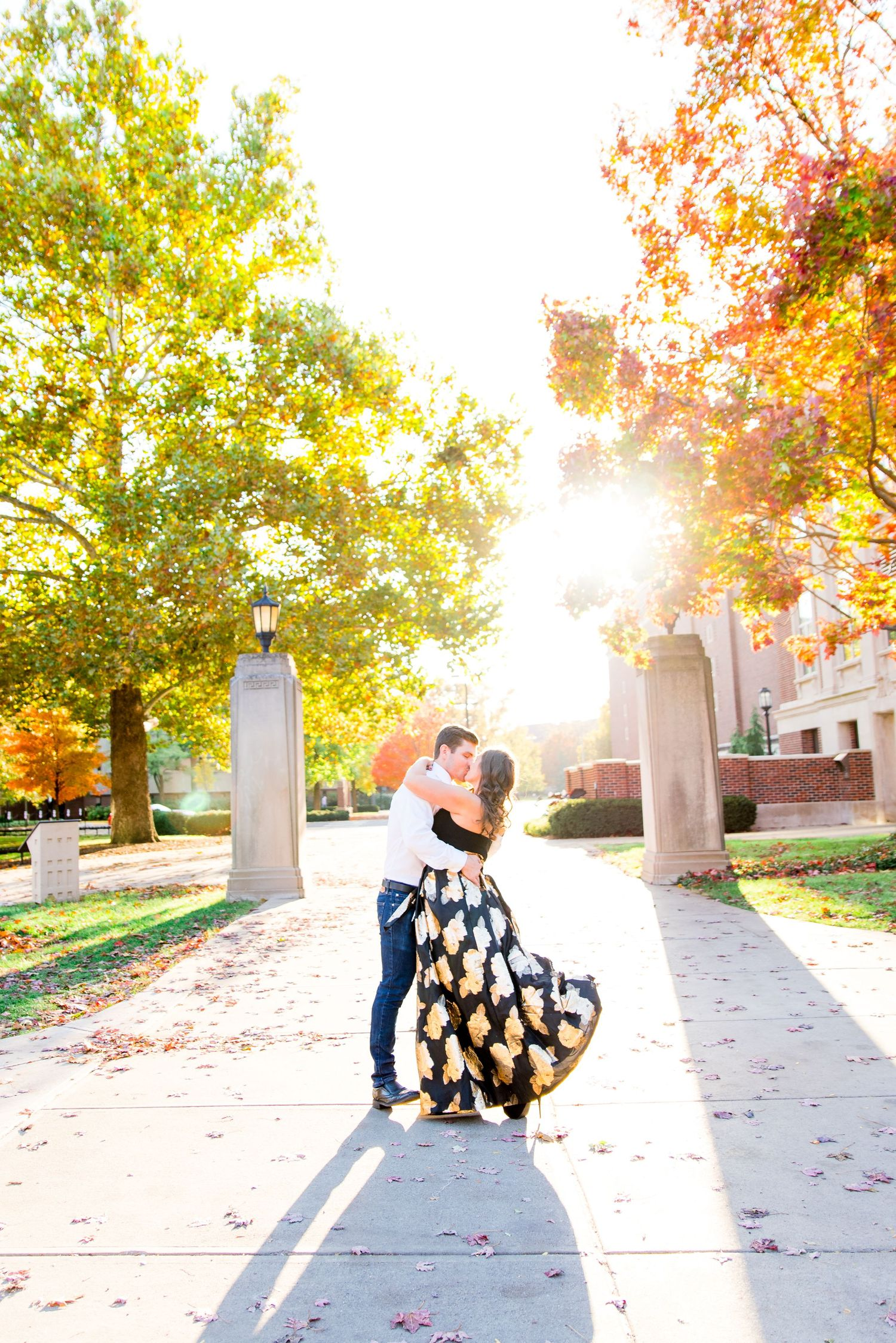 woman in black and gold skirt hugging and kissing man in white shirt at Purdue University in the fall at sunset