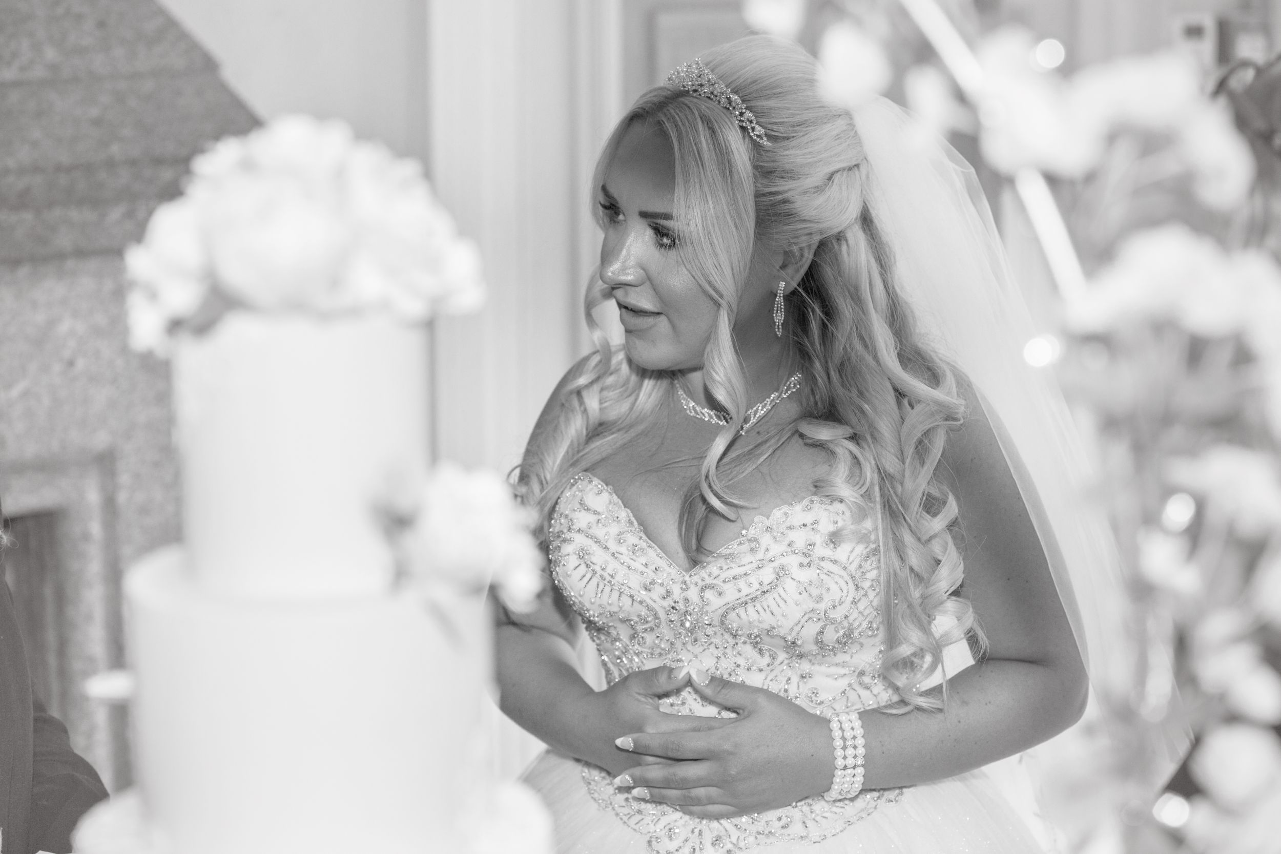 Black and white image of Bride with cake in soft focus in foreground