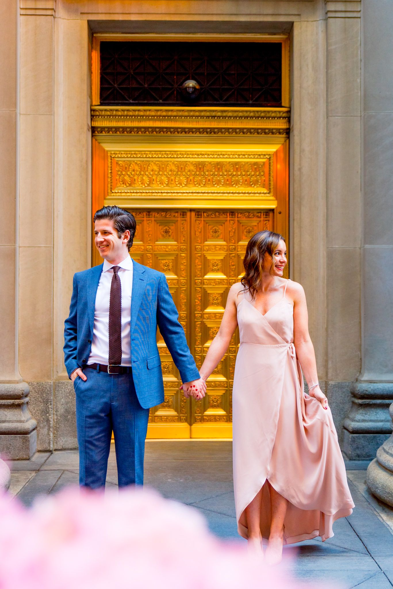 man in navy suit and woman in pink dress hold hands and look out to the sides in front of gold door in downtown Chicago