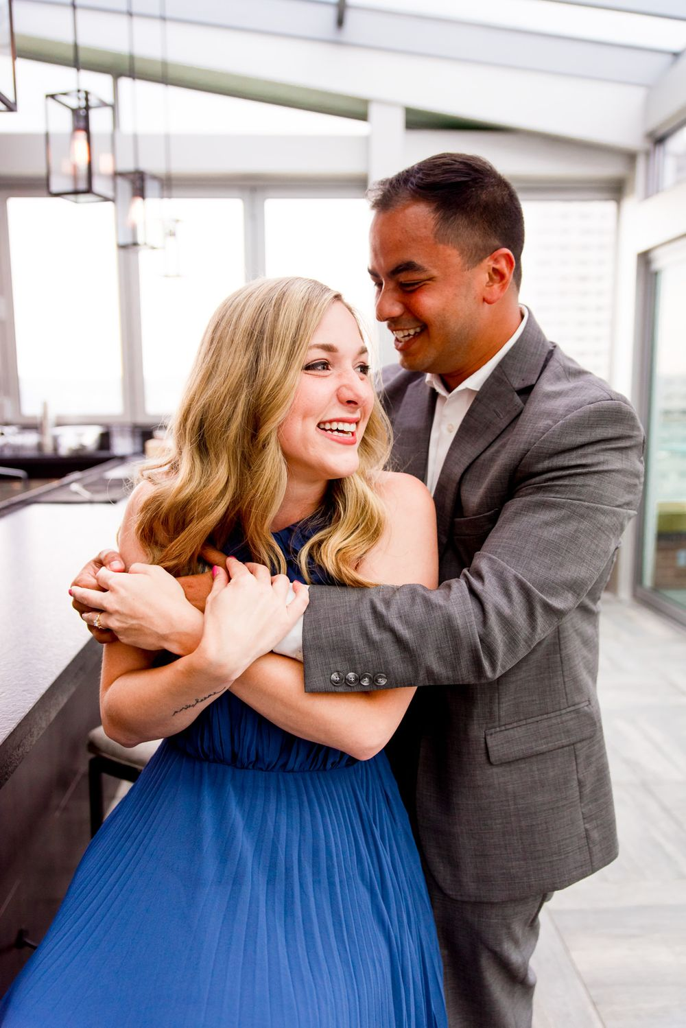 young woman with blonde hair smiles as man in grey suit hugs her from behind on the rooftop of Lytle Park Hotel