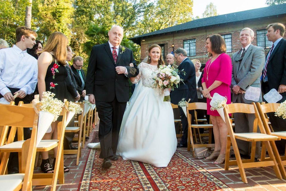 Bride Ashley is walked down the aisle by her father during her wedding ceremony at Millstone at Adams Pond in ColumbiaSC