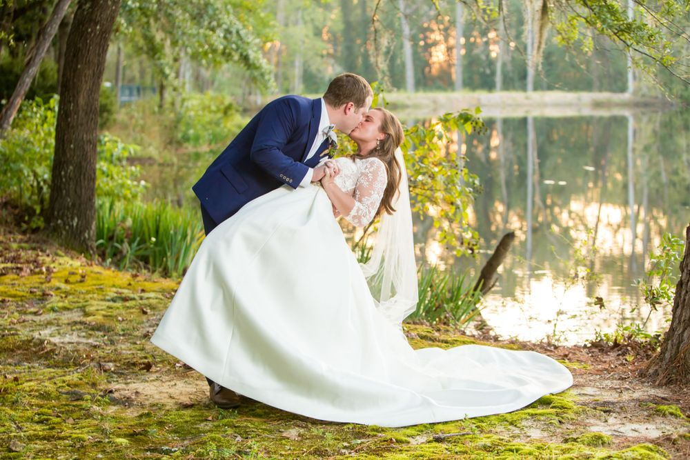 Groom Paul dips and kisses bride Ashley following their wedding at Millstone at Adams Pond in Columbia, SC