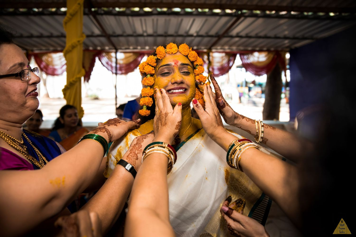 Relatives putting haldi on bride's face at a destination wedding