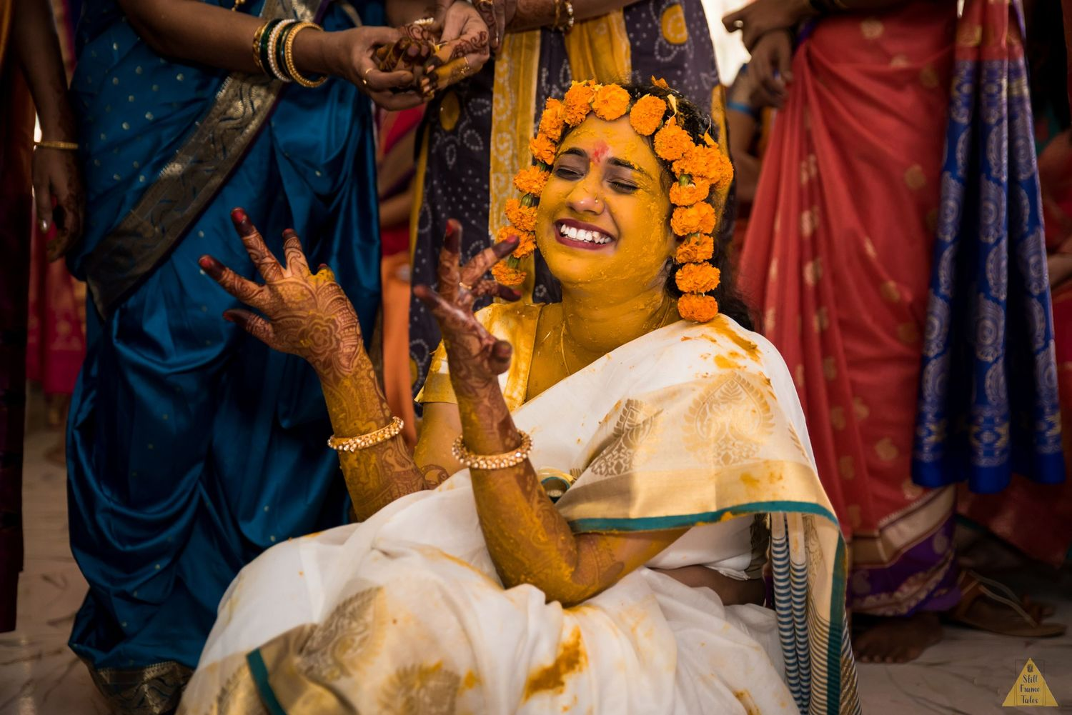 Bride laughing over a joke at her haldi ceremony