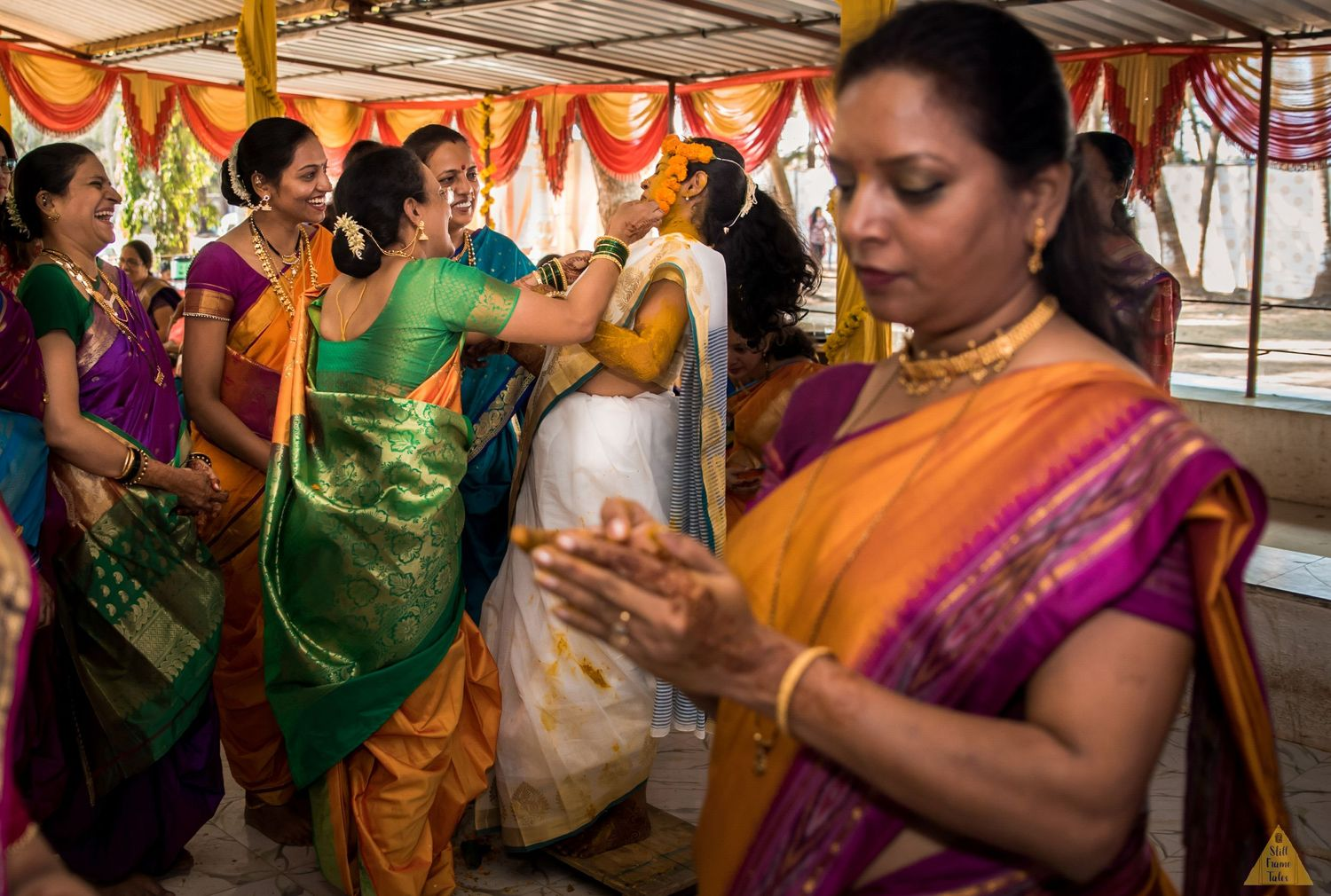 Fun moment of haldi where relatives all together putting haldi on bride's face
