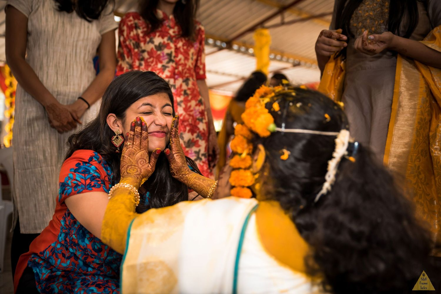 Bride and her best friend putting haldi on each others face at a destination wedding ceremony