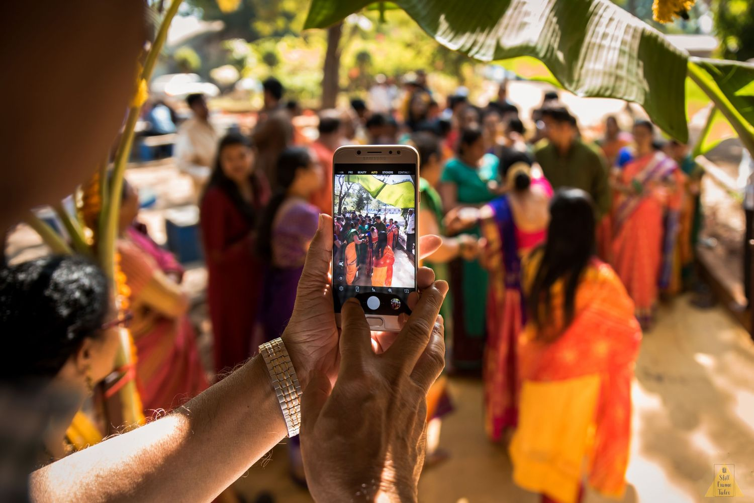 Relatives dancig and enjoying at a destination wedding while someone clicking their picture in a mobile phone