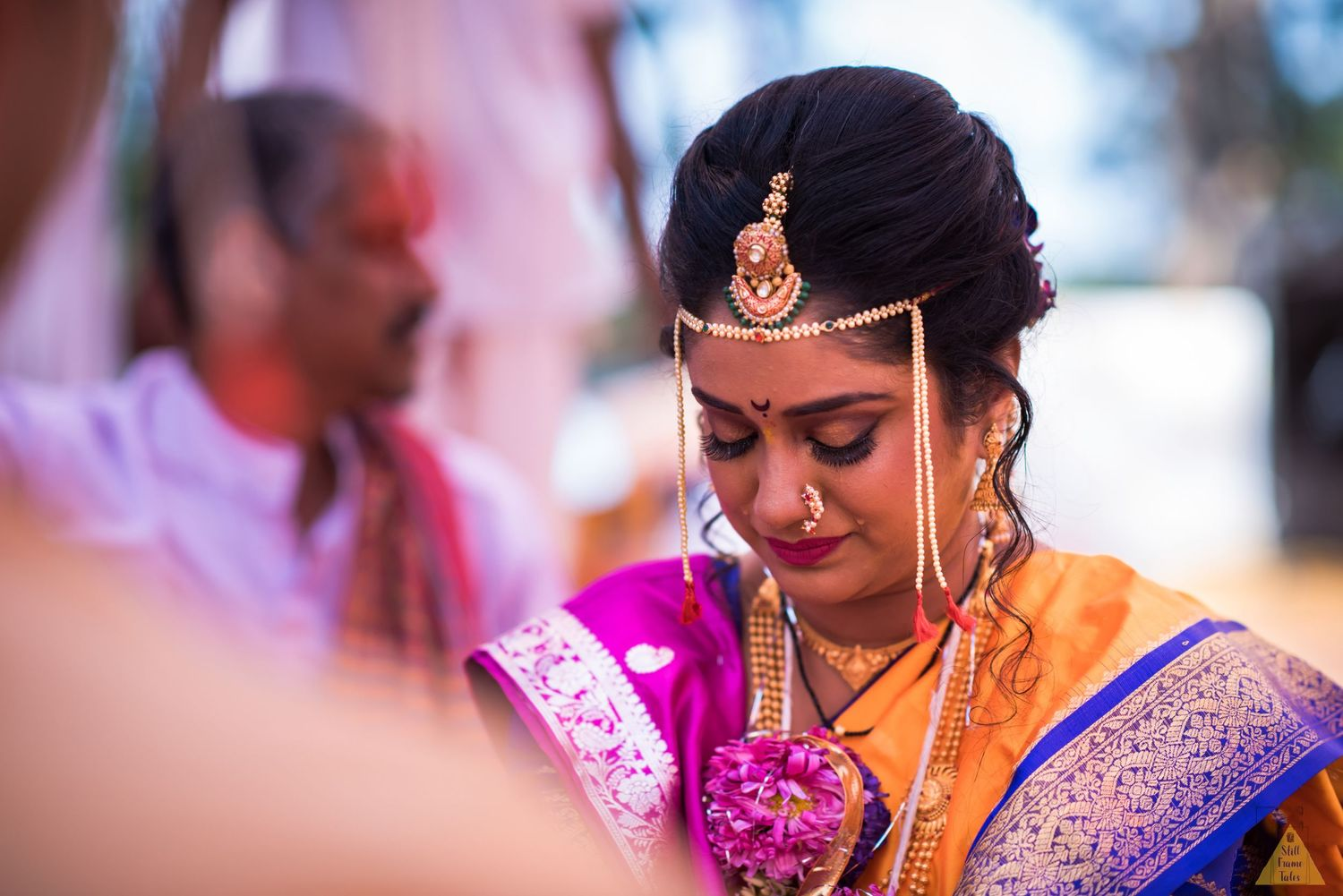 Emotional bride looking down while crying at a destination wedding ritual