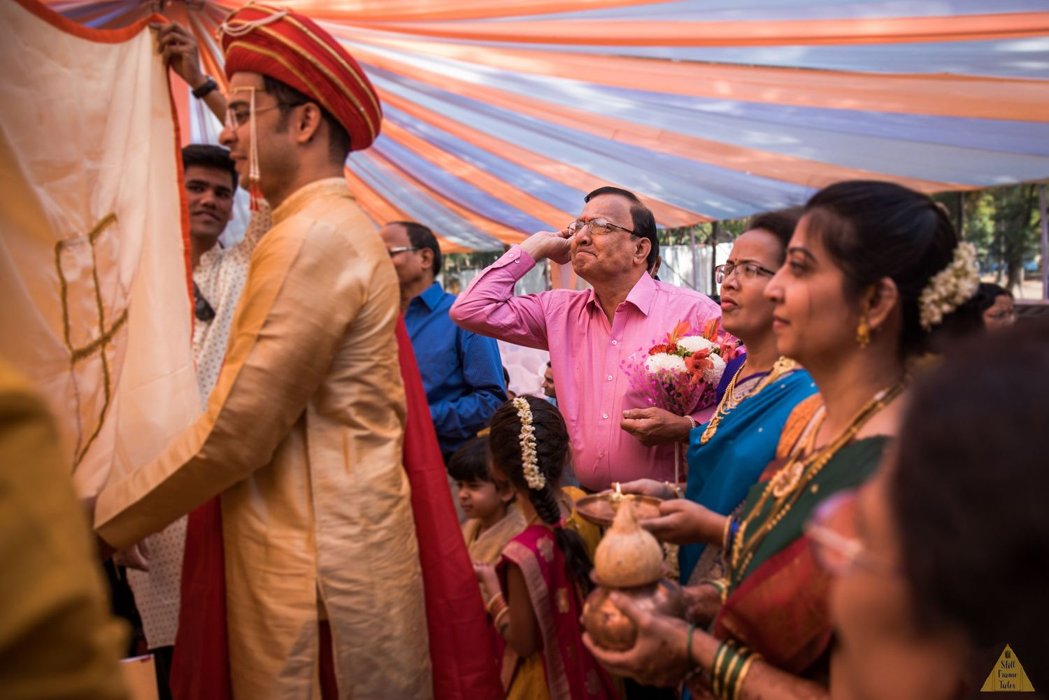 Groom's uncle showering flower petals on him at a fun wedding day varmala ritual