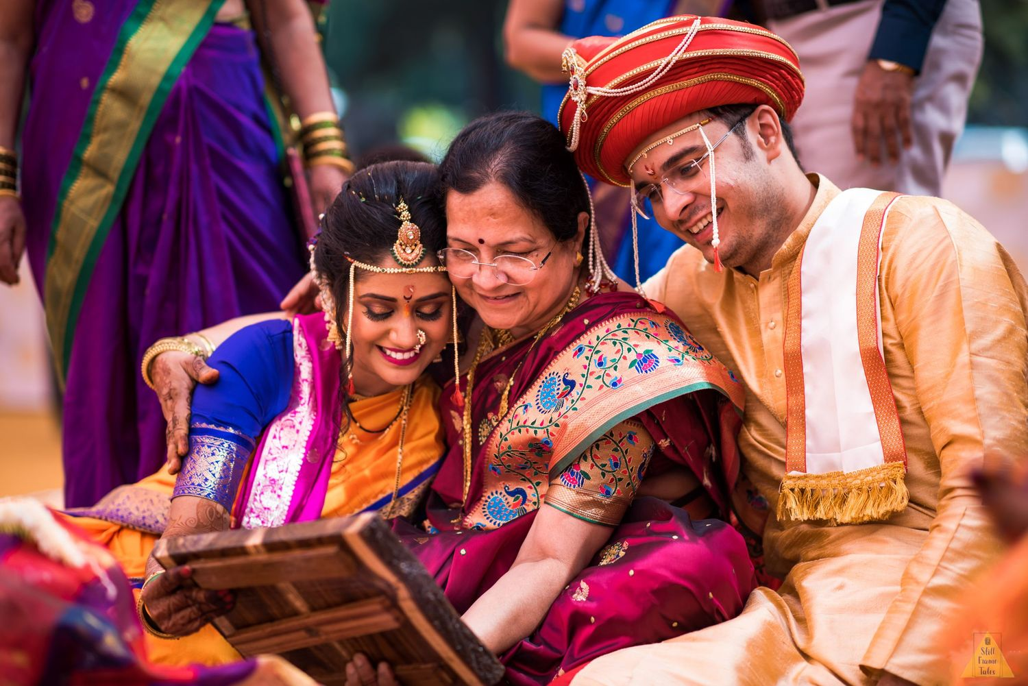 Mother cuddling couple and watching a reflection in the mirror while performing wedding day ritual