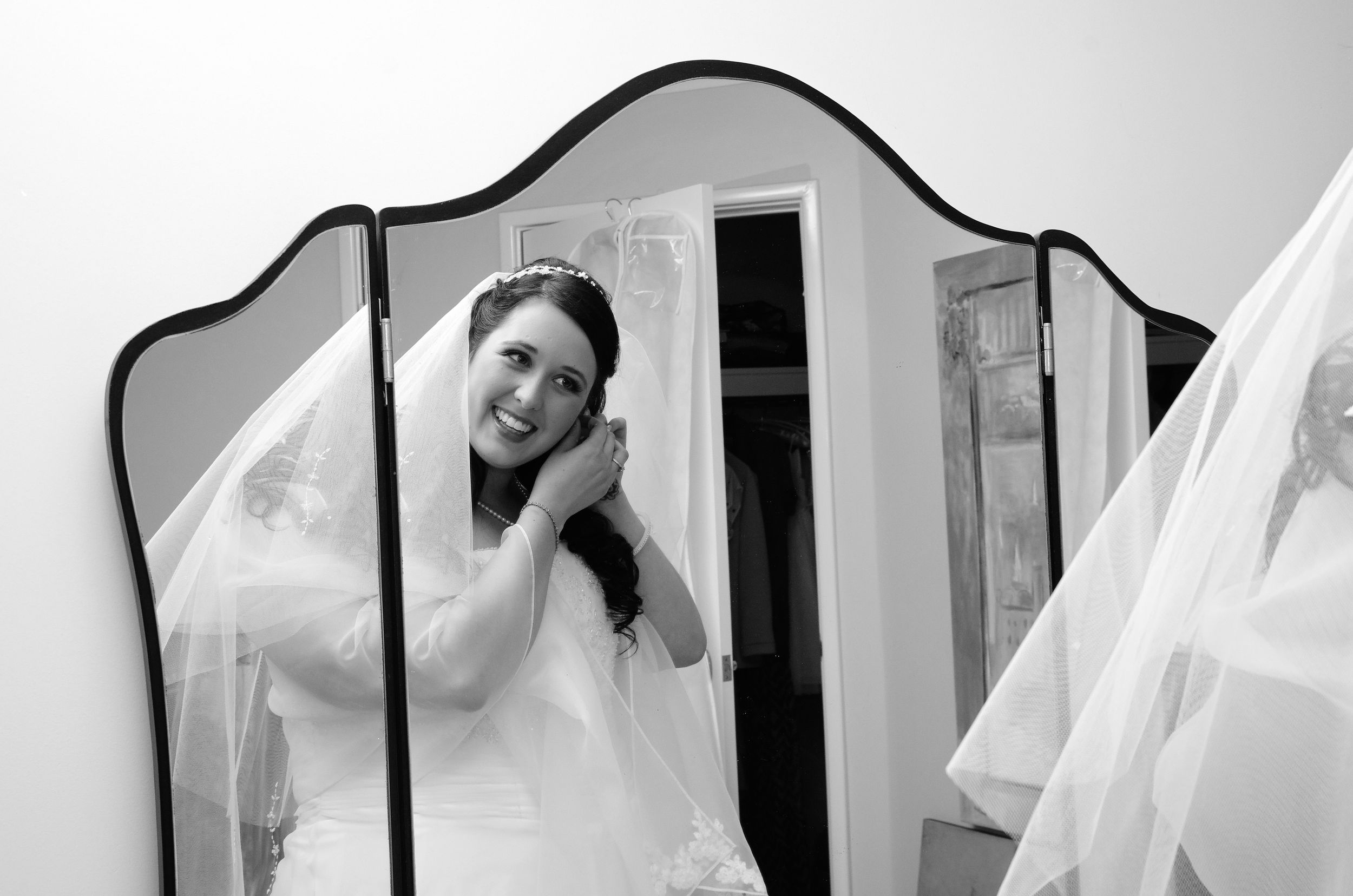bride getting ready looking at her reflection in mirror
