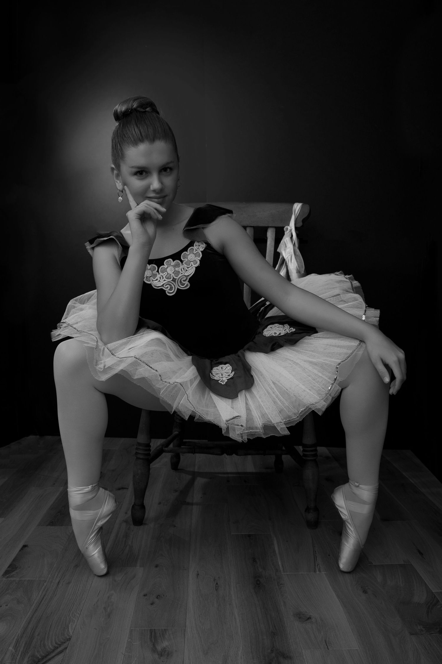 black and white image of ballerina wearing tutu, sat on chair.