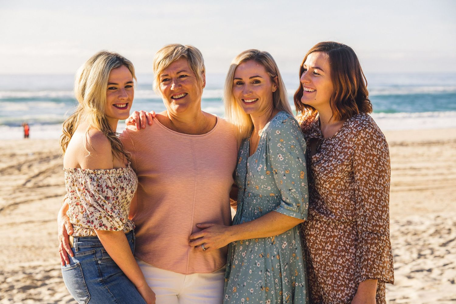 Relaxed group photo of Mum and daughters on the beach