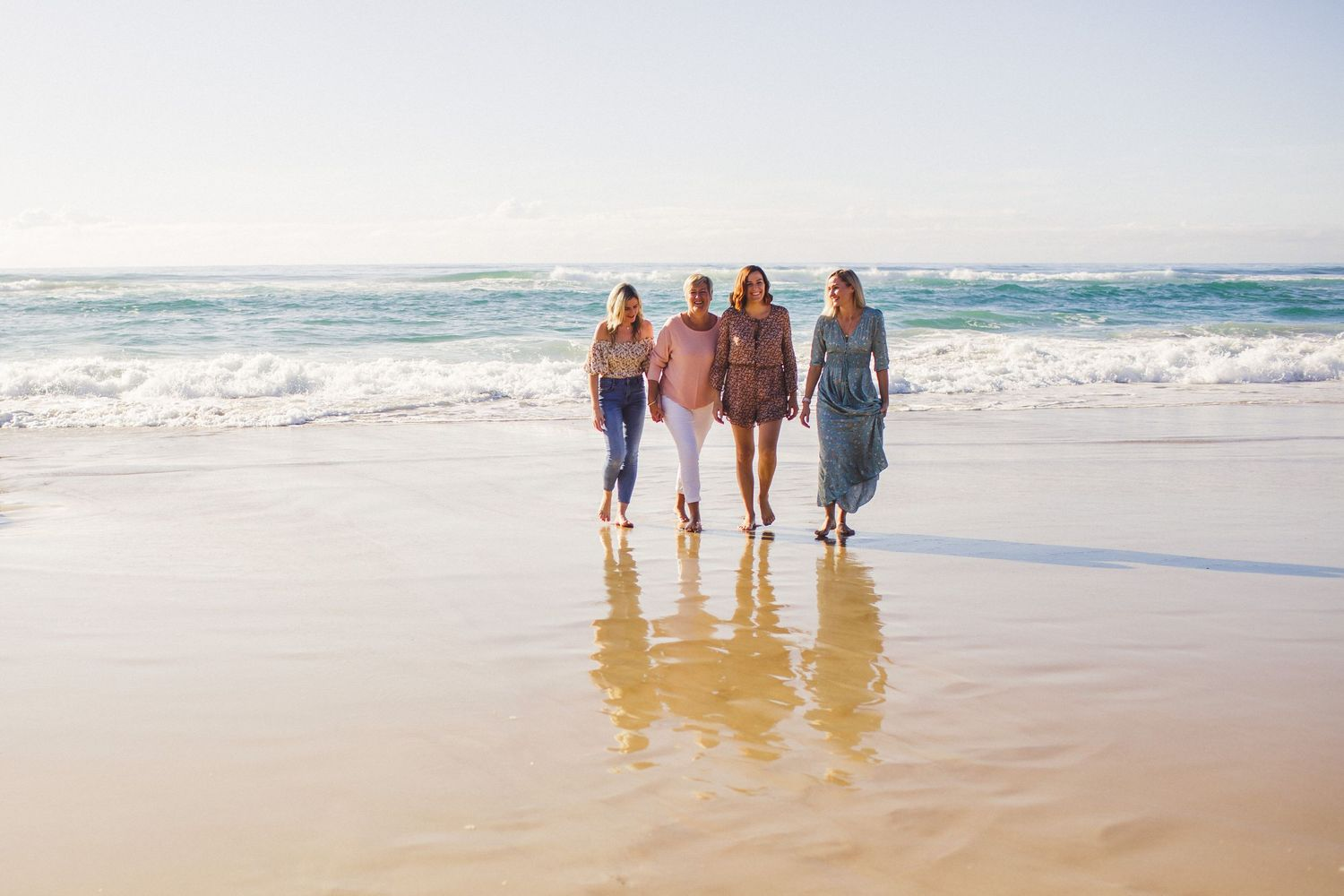 Mother and daughters walking on the beach at Burleigh