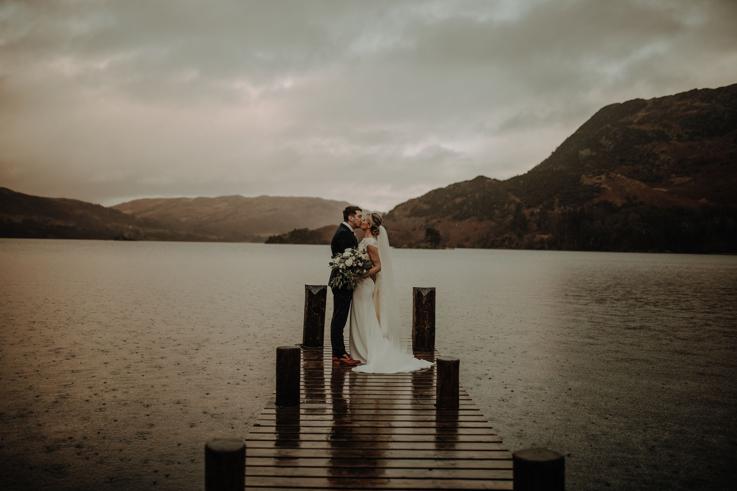 Lake District Wedding at Inn on the Lake. Bride and groom on jetty. Lake district wedding photographer. Winter wedding