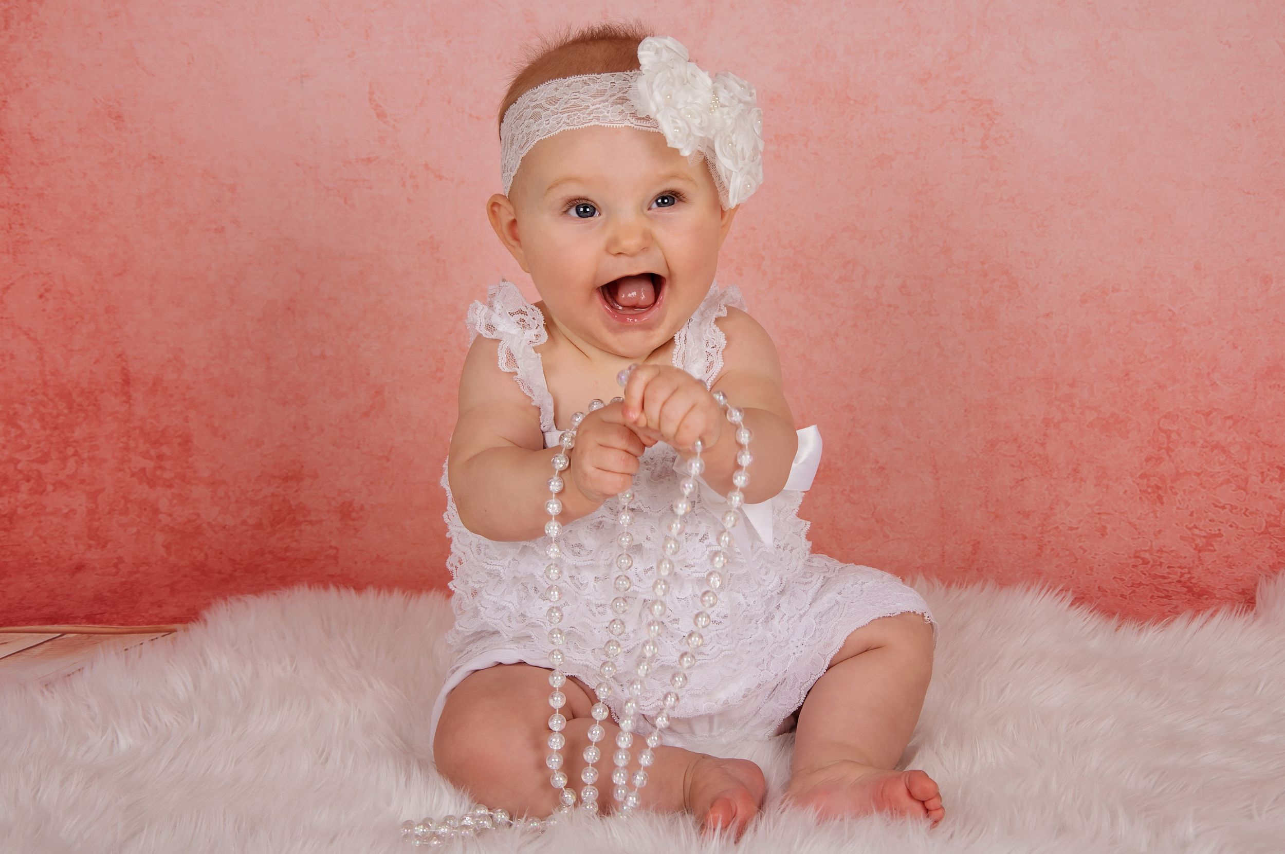 baby sitting up playing with pearls and laughing