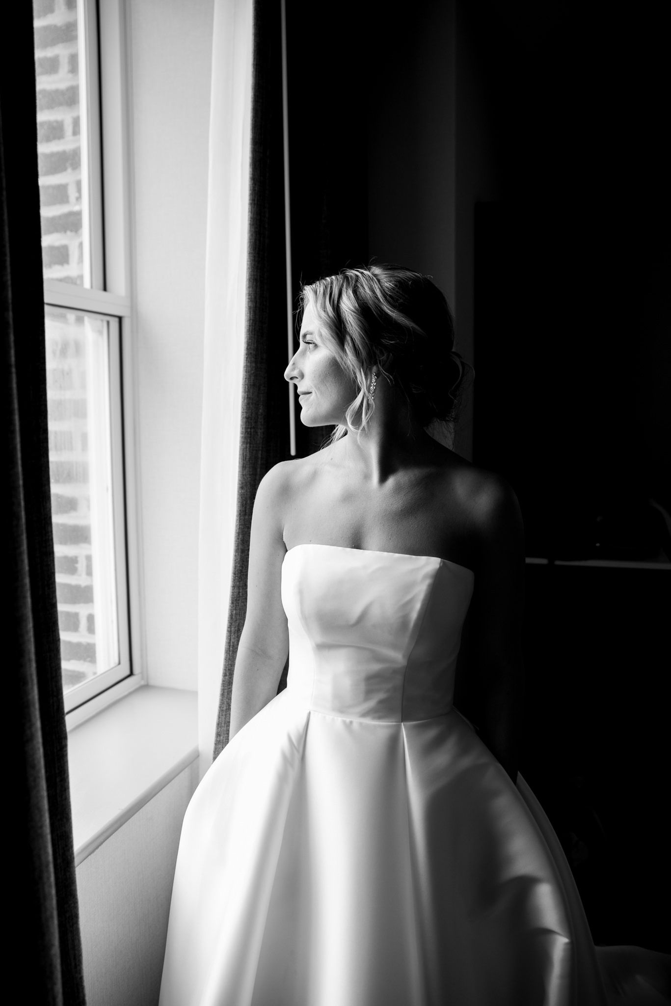 blonde bride with updo and strapless wedding dress looking out the window while getting ready