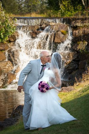Groom dipping bride in front of waterfall.