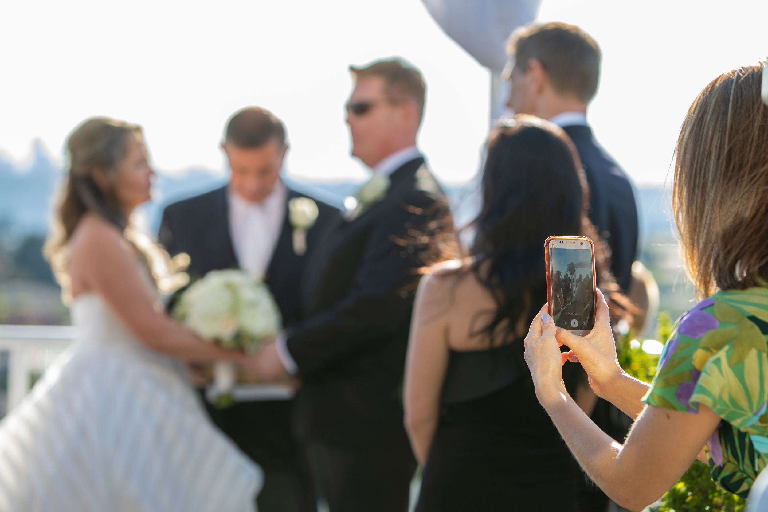 Someone recording wedding on their phone.