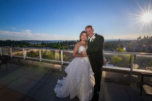 A newly married couple posing on a roof top with Bellevue in the background.