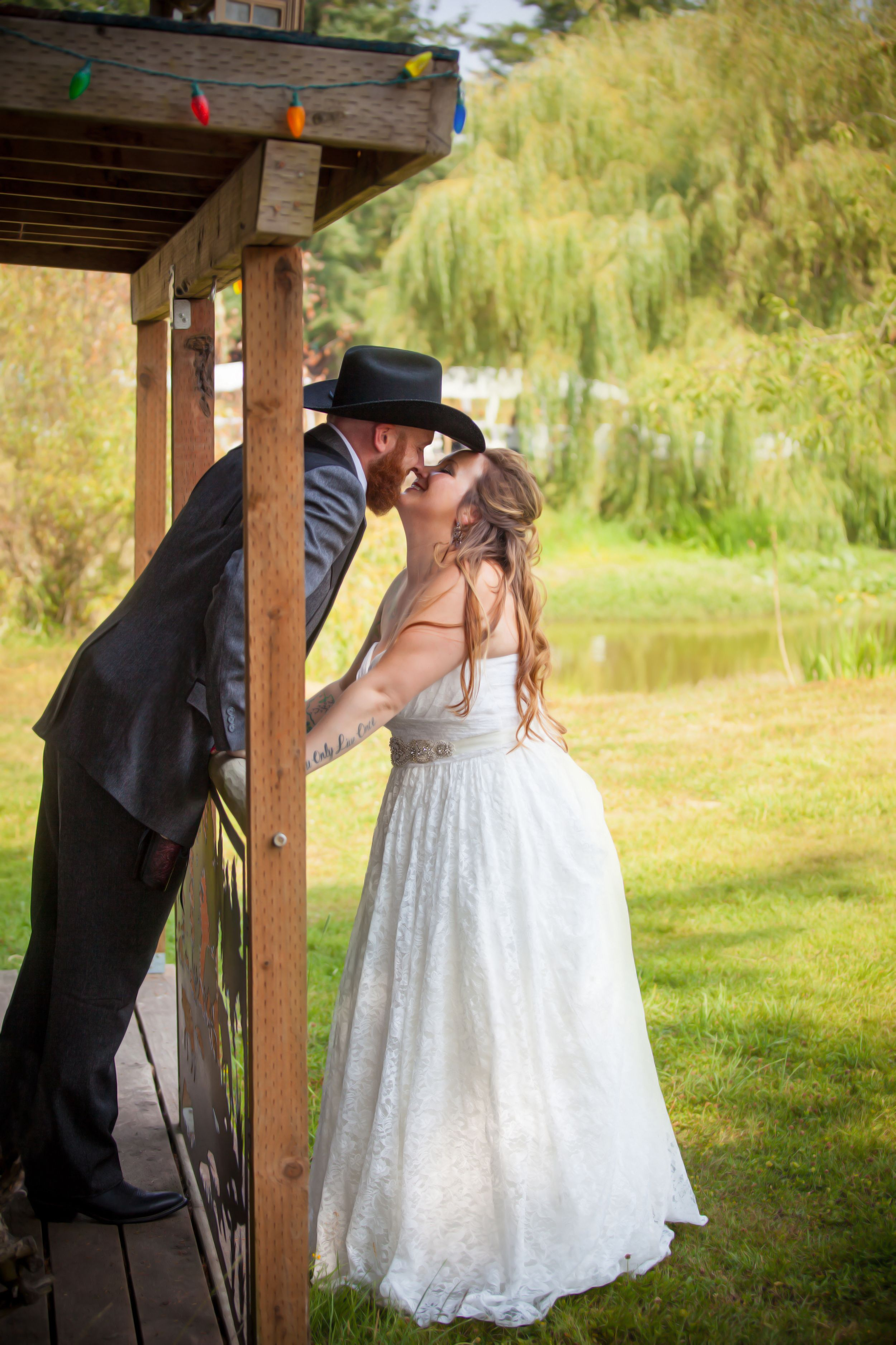 Bride and groom kissing off of a porch.