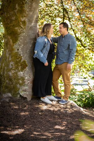 Newly engaged happy couple under a tree.