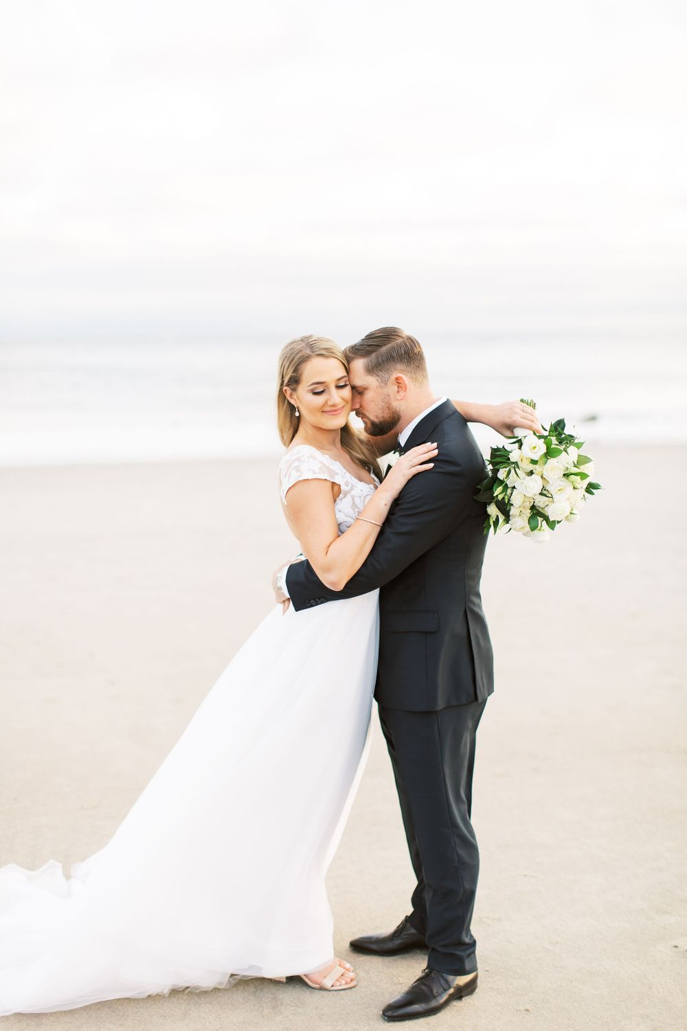 bride and groom getting close on the beach during couples portraits at the westin resort in hilton head island, sc