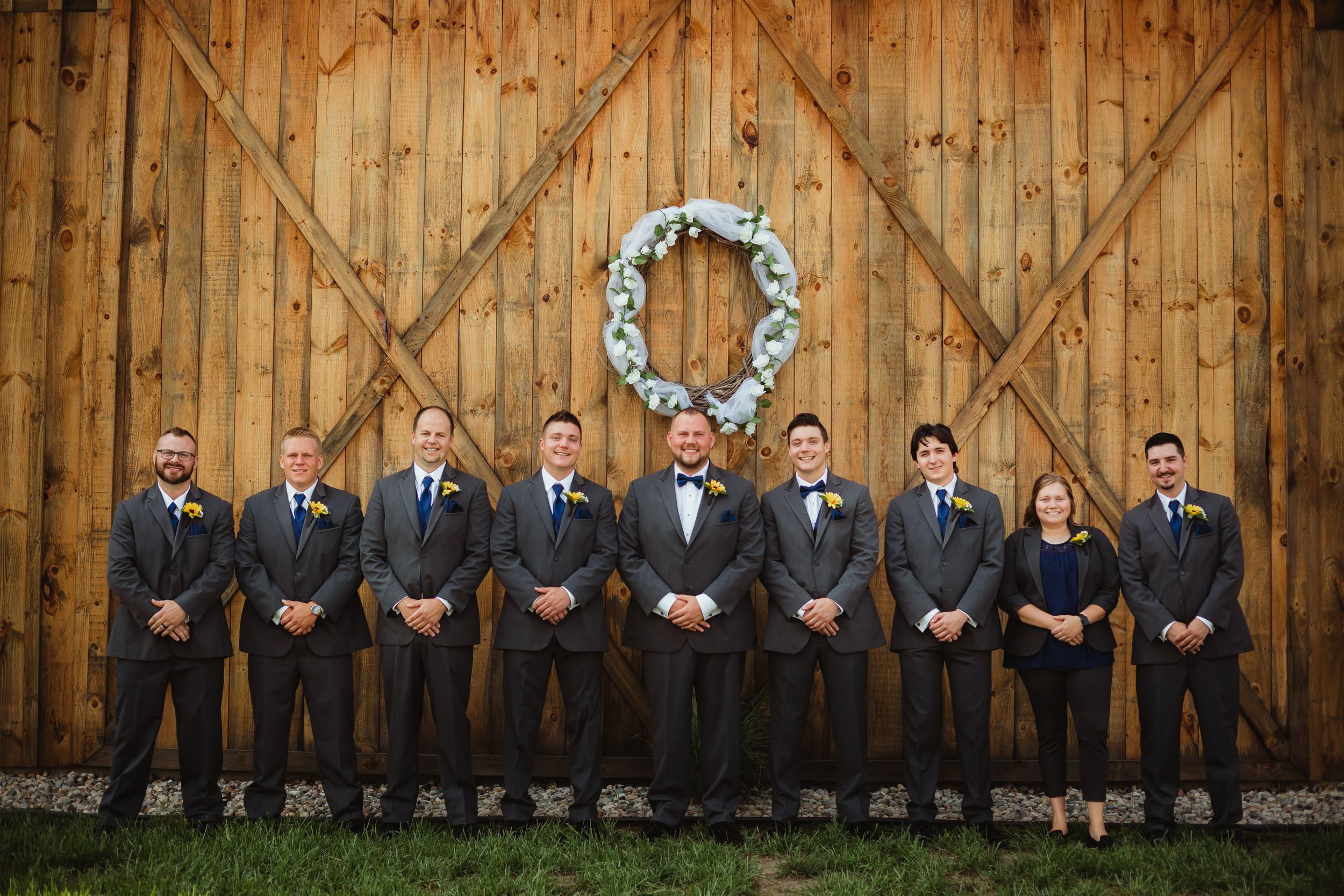Groom, groomsmen, and one woman in dark grey suits with blue ties standing in front of the barn.