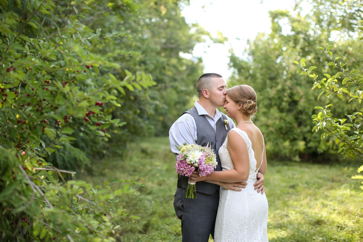 Groom kissing bride on the forehead during an apple orchard wedding