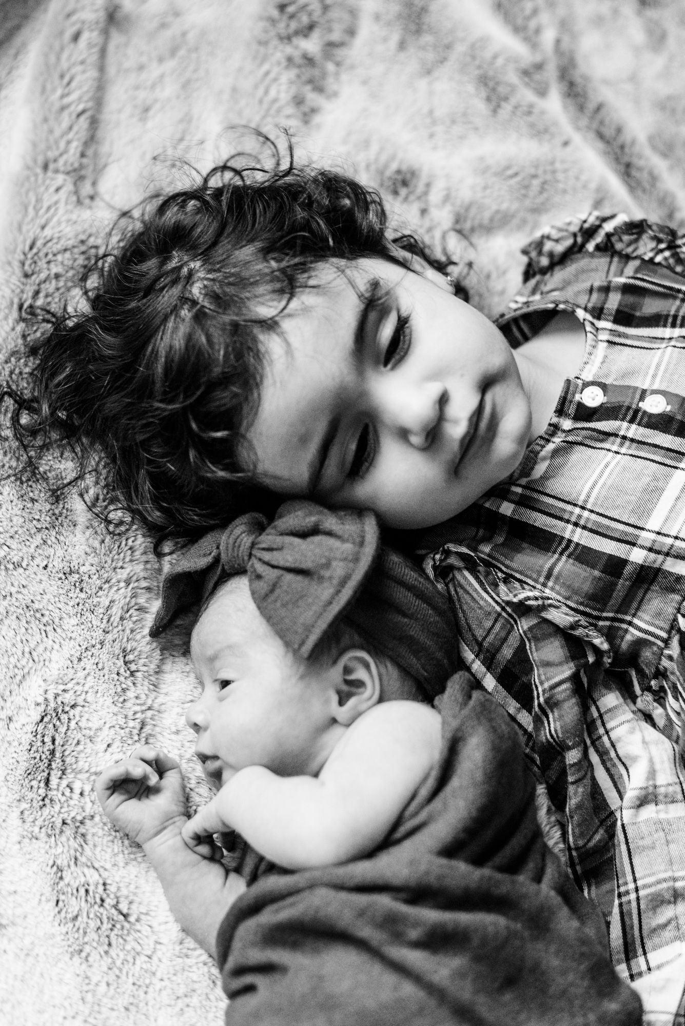 Lifestyle newborn black and white with bow with big sister in Pittsburgh, Pennsylvania