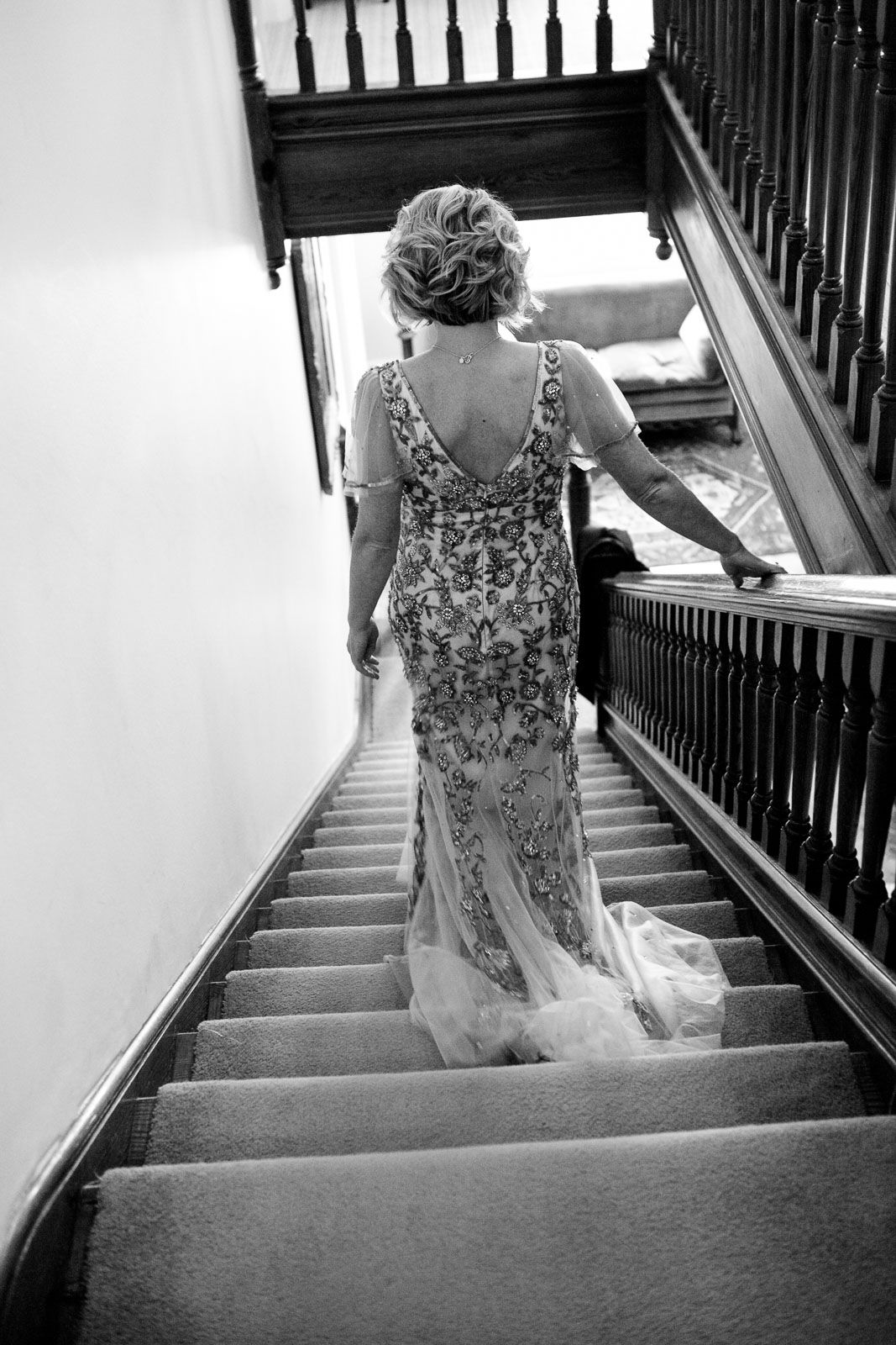 bride in embroidered dress walking down stairs