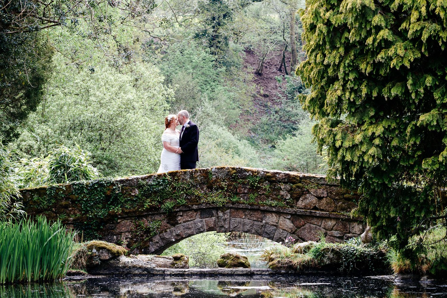 Bovey Castle wedding photographer captures image of bride and groom stood on a bridge