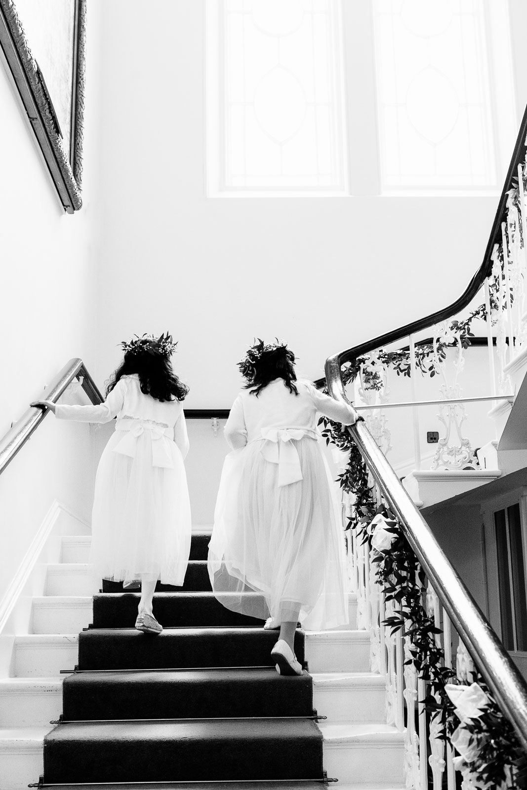cute flower girls walk up a staircase at Reed Hall Exeter wedding
