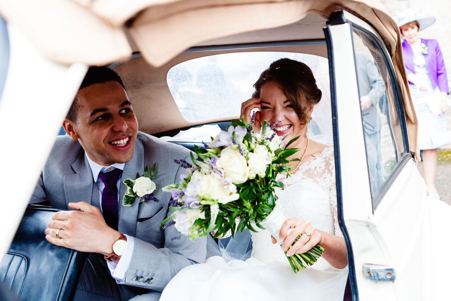 photograph of wedding couple in car after church ceremony