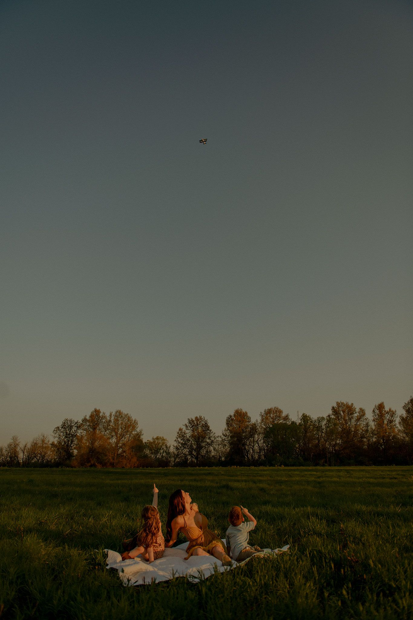 mother and young children are sitting on a blanket in the middle of a field during sunset, looking at plane