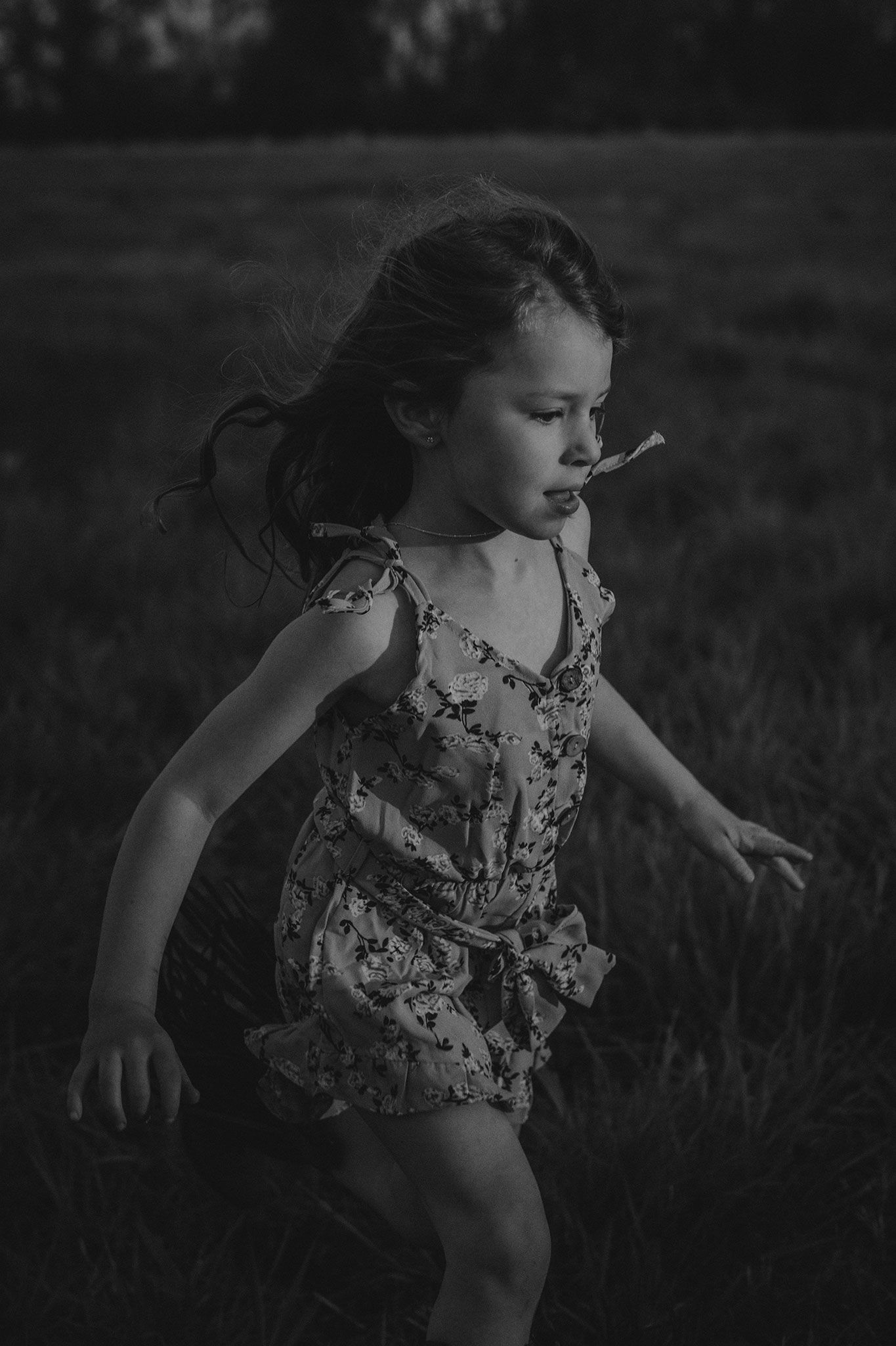 black and white image of little girl running through field at sunset